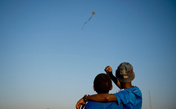 Two kids flying a kite