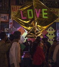 Colourful big shiny golden kite with the word love in the night market or Indian bazaar for the festival of Makar Sankranti or Uttarayan in the old area Khadia of Ahmedabad in Gujarat, India