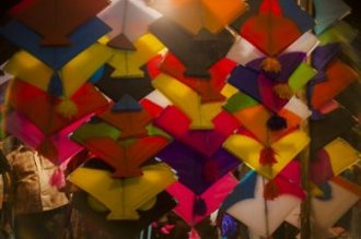 Colourful kites in pink, yellow, orange, green, blue, white colours in the night market or Indian bazaar for the festival of Makar Sankranti or Uttarayan in the old area Khadia of Ahmedabad in Gujarat, India.